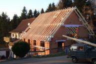 Ein fertig errichteter Dachstuhl auf einem Rohbau aus Backsteinen
