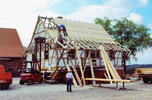 Am fertig ausgemauerten Rohbau des Fachwerkhauses wird die Dachschalung angebracht.