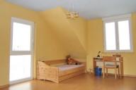 Kindertisch, Stuhl und Bett passen im großen Dachraum mit Dachgaube
