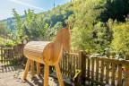 Ein Holzpferd zum Voltigieren lernen, der Gartenzaun und das Vogelhäuschen